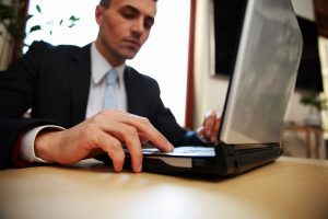 Businessman working on a laptop undertaking 7 steps for promoting a blog